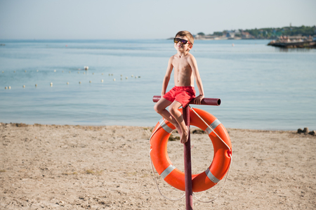 healthy little boy in sunglasses sitting on beach with lifebuoy in summer sunny day
