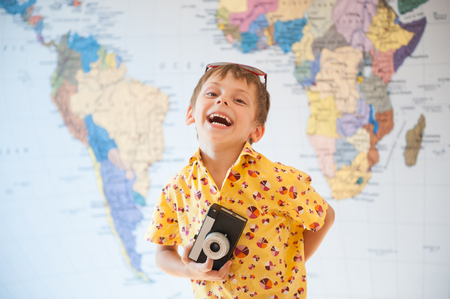 happy laughing kid in yellow shirt with old retro camera in hand on map background