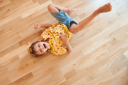 funny laughing caucasian little boy rolls on floor with laughter holding his stomach Stock Photo