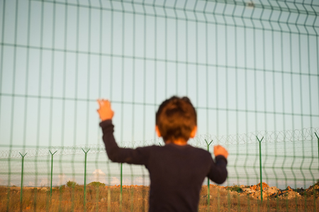 one little poor kid refugee holding high fence on border looking into far distance