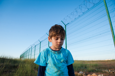 upset little boy refugee with dirty face near wall fence on border Stockfoto