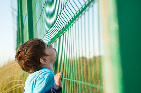 poor little caucasian child refugee looking up for freedom holding cage fence on border