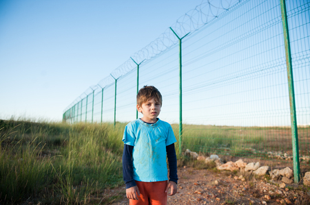 suffering refugee child with dirty face near high fence on state border in desert