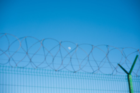 state border fence with barbed razor wire on blue sky and moon background Stock Photo