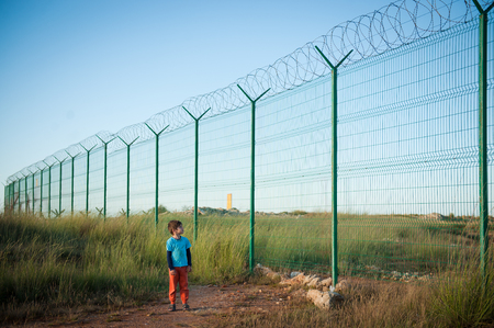 lonely little caucasian kid refugee watching at high fence with barbed razor wire desert Reklamní fotografie