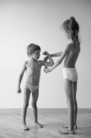 slim healthy caucasian little girl examines strong small boy muscle with measuring tape black and white photo