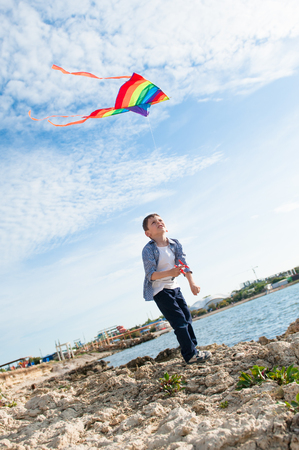happy active little kid playing with flying kite near sea shore at summer sunset