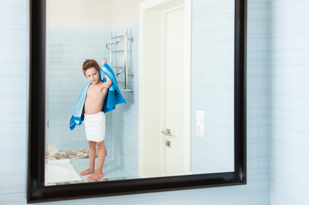 adorable healthy small child dry off his body with blue towel in morning bathroom