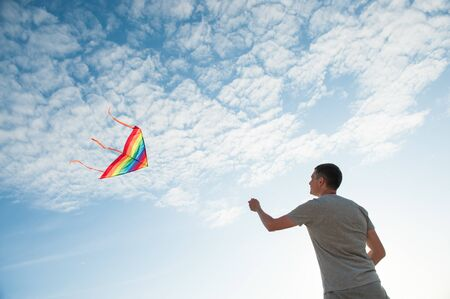 happy healthy caucasian male with flying kite on blue sky with clouds background outdoor