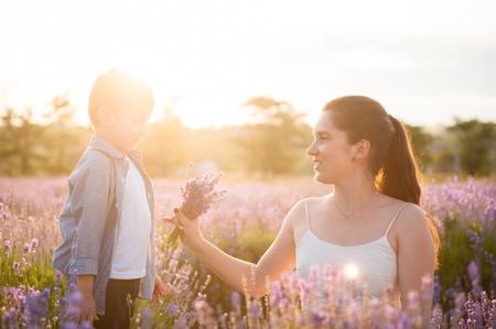 happy caucasian woman with bouquet looking at her beautiful son among outdoor nature Stok Fotoğraf - 122663663