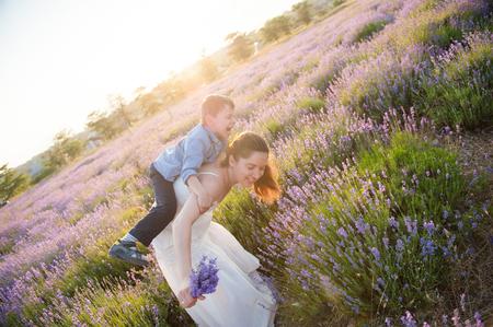 funny little boy sitting on mother back playful in summer lavender field