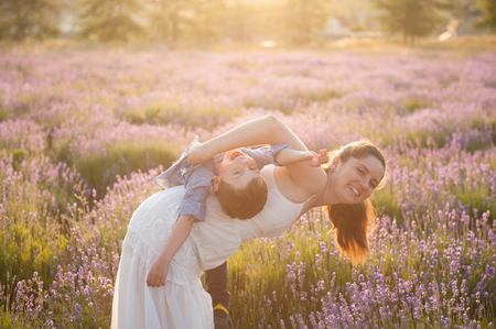 beautiful family consisting mother and kid playing in summer flower field Stok Fotoğraf - 122663665