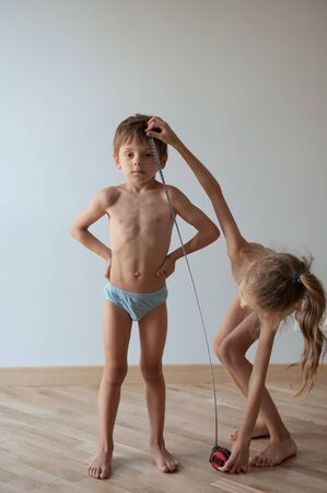 thin little girl measuring small strong healthy brother boy height with tape indoors Stok Fotoğraf
