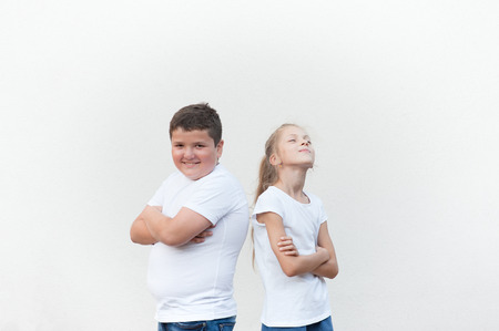 happy handsome caucasian kids in white shirts fat boy and thin girl back to back on bright background Stock Photo