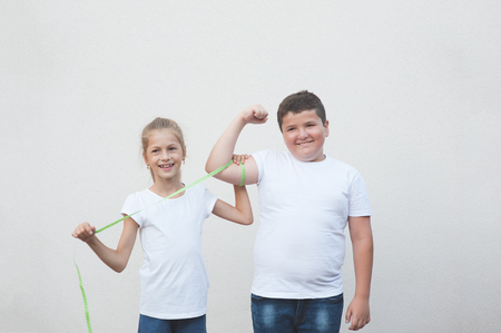 beautiful happy slim caucasian little girl measuring cute thick boy big muscle with tape Imagens