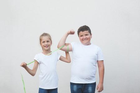 beautiful happy slim caucasian little girl measuring cute thick boy big muscle with tape 版權商用圖片