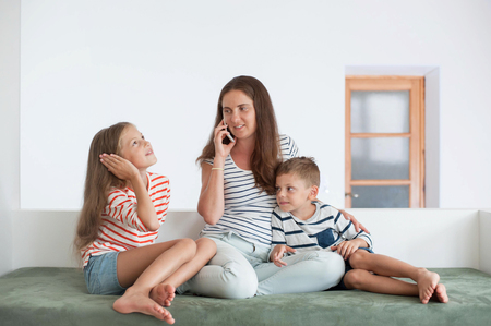 happy family consisting of three caucasian person mother call mobile phone kids imitate