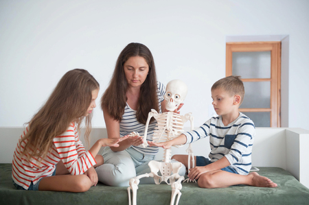 mother with kids studying human anatomy using skeleton as example Stok Fotoğraf