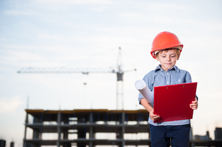 cute little boy in helmet with paper blueprint and folder in hands on building site Stok Fotoğraf