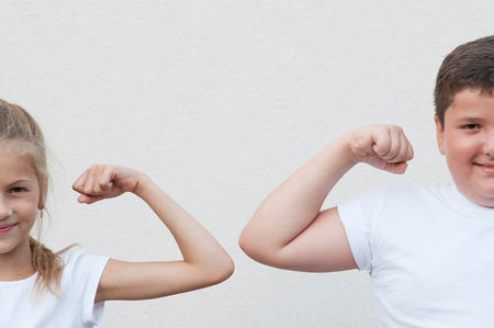 two happy beautiful caucasian kids fat boy and thin girl showing muscles on copy space backdrop