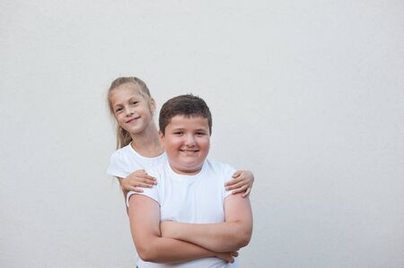 beautiful happy smiling kids thin caucasian girl in white shirt hugging fat boy copyspace