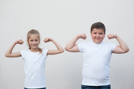 two children little thin girl and thick boy showing their muscle on copyspace background
