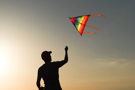 silhouette of healthy male playing flying colorful kite in autumn sunset