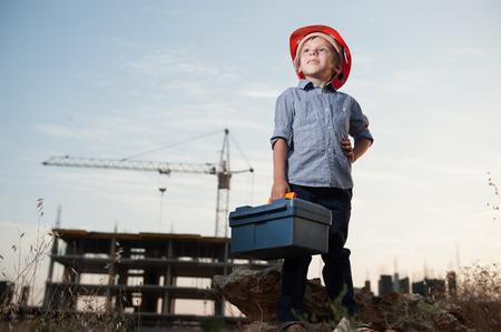 mignon petit enfant dans un casque de constructeur avec une boîte à outils à la main sur un chantier de construction debout