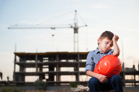 cute upset little boy sitting near building site with orange helmet in hands