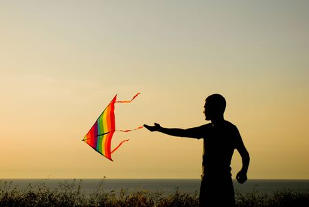 silhouette of adult healthy man playing flying colorful kite in autumn sunset Stok Fotoğraf