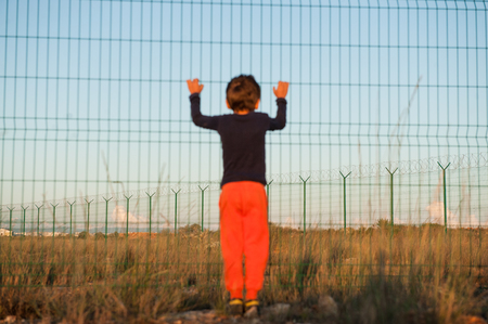 poor suffering little boy refugee in orange pants holding high fence on state border