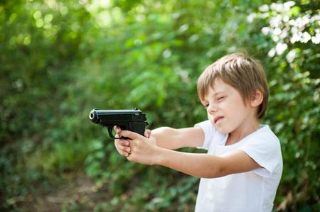 cute little boy in white shirt taking aim with black gun in green forest copyspace