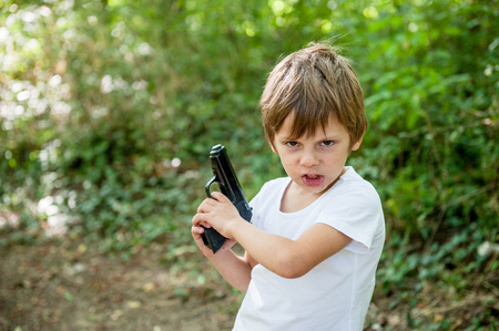 angry small caucasian boy with grimace on his face holding real black gun outdoors