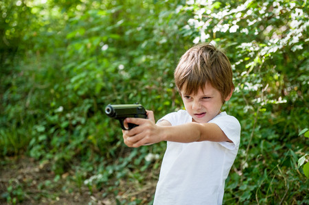 little kid sniper point gun in target carefully aiming outdoors on green treees background Stock Photo