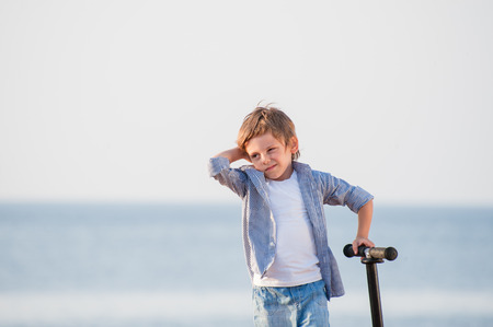 strange cute little boy with grimace on his face with scooter on sea autumn shore Stock Photo