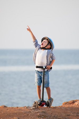 happy healthy kid in helmet with scooter raised index finger up as a sign of victory