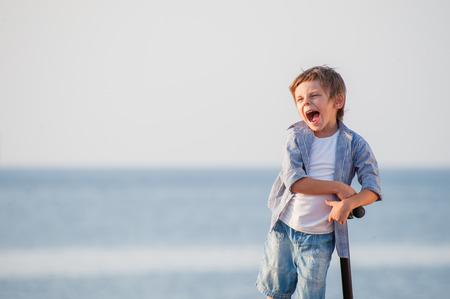 happy delightful cute caucasian little boy with scooter on autumn sea backdrop copy space