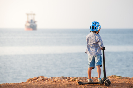 sport athletic little boy in blue helmet with scooter watching at ocean horizon with ship