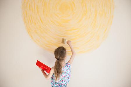 thin little girl drawing art work yellow sun on wall with brush Banco de Imagens