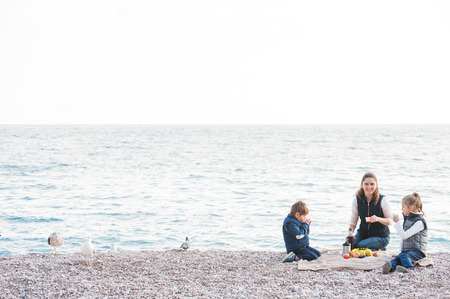 happy family in jackets consisting of three person on sea shore picnic in cold weather