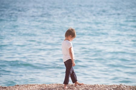 pensive sad caucasian lonely small boy walking along sea coast beach in autumn season Stock Photo