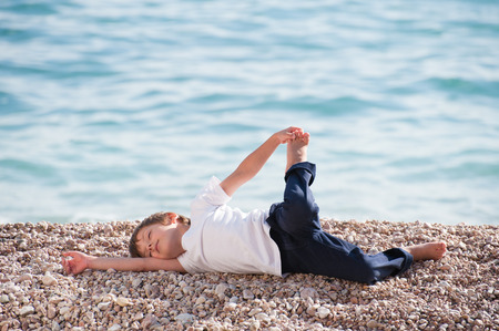 healthy small kid in shirt and pants making relaxation exercises on sea shore in autumn Standard-Bild