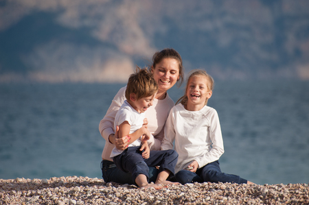 happy laughing caucasian family mother and two kids sitting on ocean shore in autumn