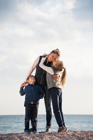 happy caucasian family mother and two kids kissing her in autumn jackets on sea coast Stok Fotoğraf - 116437924