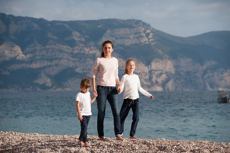 healthy caucasian mother and two kids walking on sea coast on autumn spring sunset Stok Fotoğraf - 116437923