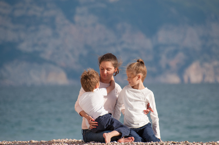 happy caucasian family mother and two children on sea shore in autumn or spring Stok Fotoğraf