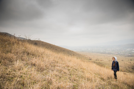 one lonely caucasian small girl in jacket with hood in overcast mountain on slope Фото со стока
