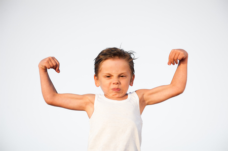funny little caucasian kid with grimace on his face showing biceps muscle with copyspace