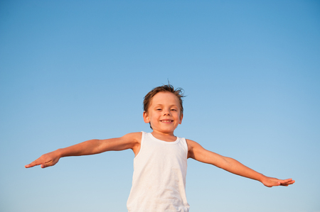 handsome happy small kid in white shirt on blue sky background