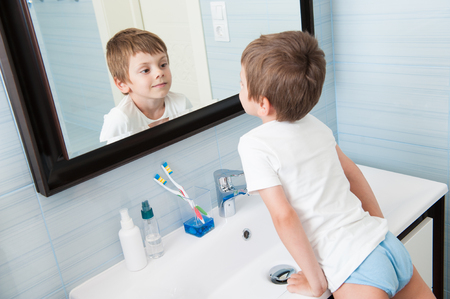handsome healthy small caucasian boy watching at his reflection in mirror in bathroom